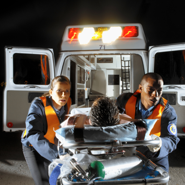 Two young paramedics wheeling a male patient on a stretcher out of an ambulance