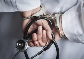 Female Doctor or Nurse In Handcuffs and Lab Coat Holding Stethoscope.